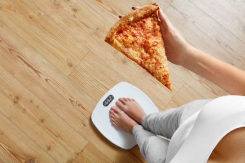 48712180 - diet and fast food concept. overweight woman standing on weighing scale holding pizza. unhealthy junk food. dieting, lifestyle. weight loss. obesity. top view