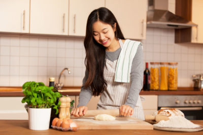 38300636 - asian smiling woman is baking bread in her home kitchen