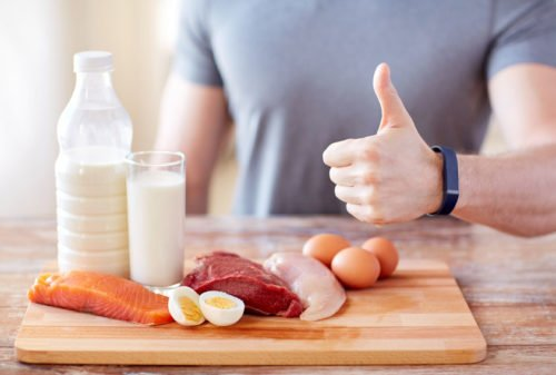 53578415 - sport, fitness, healthy lifestyle, diet and people concept - close up of man with food rich in protein showing thumbs up